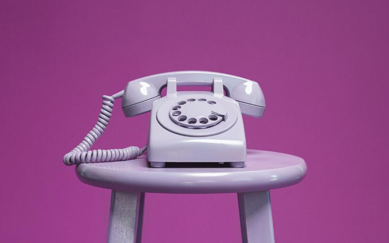 En analog telefon mot lila bakgrund
